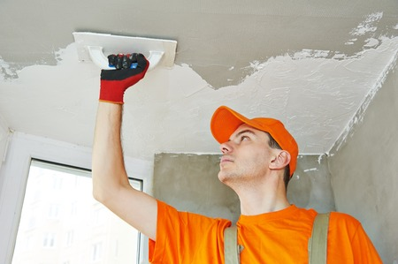 parget: Plasterer at indoor ceiling renovation decoration with float and plaster