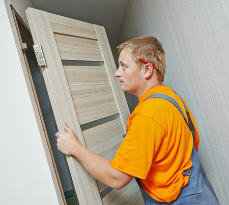 deadbolt: Male handyman carpenter at interior wood door installation