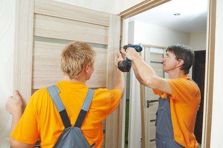 Two male workers carpenters at internal door installation Reklamní fotografie