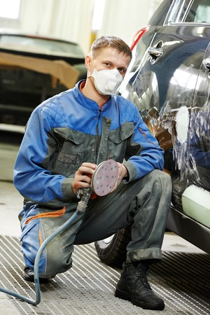 body painting: auto repairman worker in automotive industry examining car body painting or repaint at auto repair shop Stock Photo
