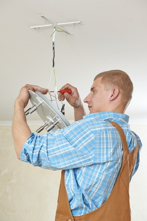 wirework: electrician working with cable mounting new wiring and ceiling lamp in home Stock Photo