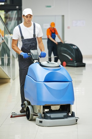 Cleaner male man workers with mop in uniform cleaning corridor pass or hall floor of business building Foto de archivo