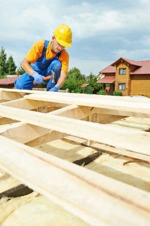 construction roofer carpenter worker hammering wood board with hammer and nail on roof installation work Stock Photo