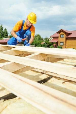 trussing: costruzione conciatetti carpentiere operaio martellare tavola di legno con martello e chiodi su lavori di installazione sul tetto