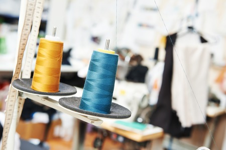 garment industry: tailor sewing concept, reals of thread in workshop