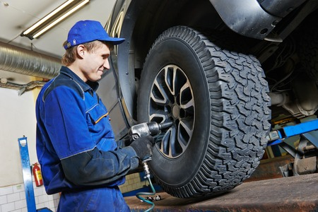 adjustment: car mechanic screwing or unscrewing car wheel of lifted automobile by pneumatic wrench at repair service station