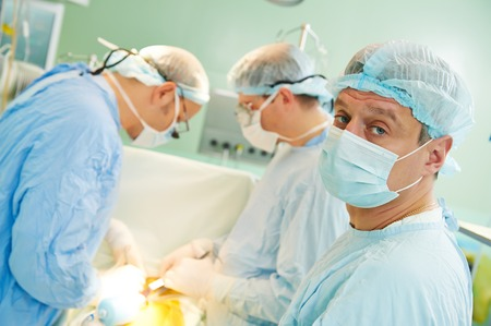 transplantation: surgeons in uniform perform heart transplantation operation on a patient at cardiac surgery clinic
