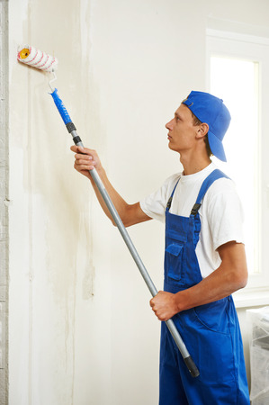 priming paint: painter with paint roller making wall prime coating  at home repair renovation work