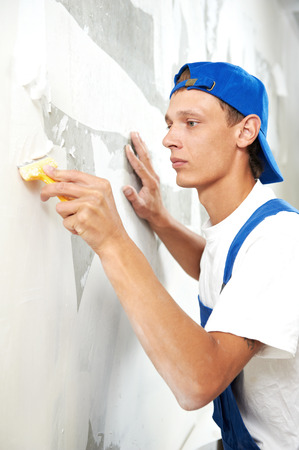 painter worker peeling off wallpaper from wall during interior home repair renovation work photo
