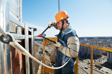 steeplejack: worker builder clinching facade construction for big tile on a building with riveting hammer