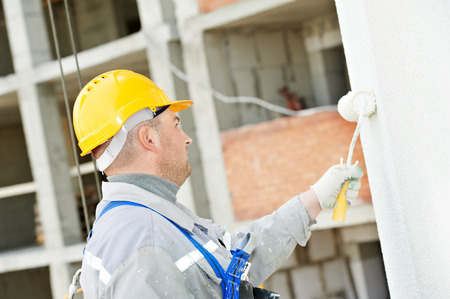 steeplejack: builder worker painting facade of high-rise building with roller