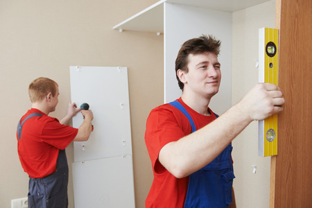 marking up: Two carpenters workers joint and settle home built-in cupboard Stock Photo