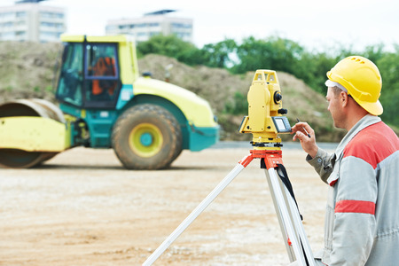 One surveyor worker working with theodolite transit equipment at road construction site outdoors photo