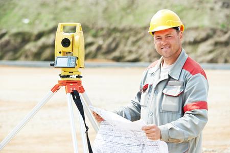 Een landmeter werknemer het werken met theodoliet transit apparatuur op weg bouwplaats buitenshuis