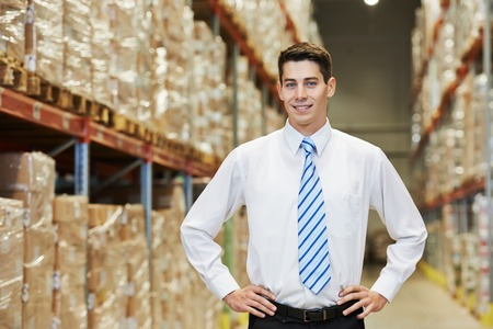 order shipping: male manager man worker standing in big modern warehouse