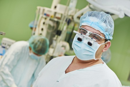 cardiosurgery: Female surgeon in uniform in front of surgery operation room at clinic