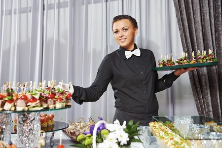 waiter: Waiter with meat dish serving catering table with food snacks during party event Stock Photo