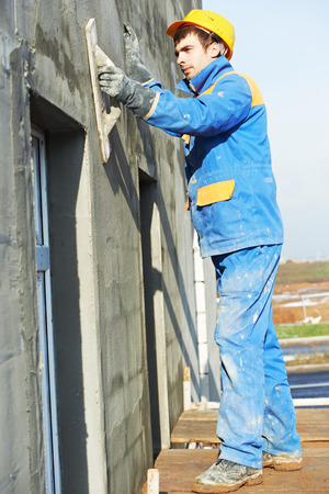 builder worker plastering facade industrial building with putty knife float photo