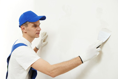 male plasterer at indoor wall renovation decoration with spatula and plaster