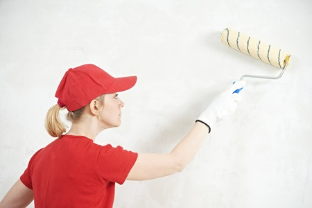 priming paint: female house painter worker painting and priming wall with painting roller Stock Photo