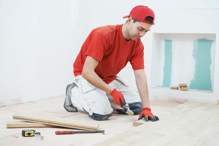 Travailleur charpentier installation bois planche de parquet au cours plancher de travail avec un marteau Banque d'images - 37008906