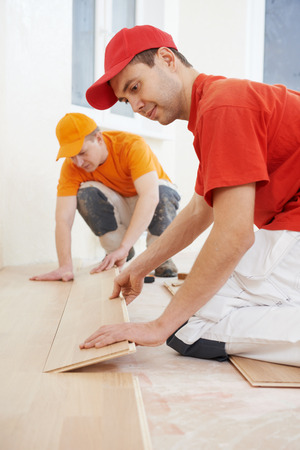 flooring cork: Two parquet carpenter workers installing wood board during flooring work Stock Photo