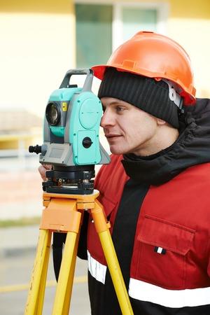 teodolito: Un trabajador agrimensor trabajando con equipos de tr�nsito teodolito en el sitio de la construcci�n de carreteras en exteriores