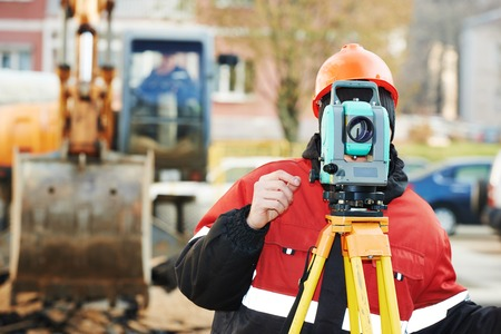 measuring instruments: One surveyor worker working with theodolite transit equipment at road construction site outdoors