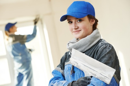 female plasterer painter portrait at indoor wall renovation decoration stopping with spatula and plaster