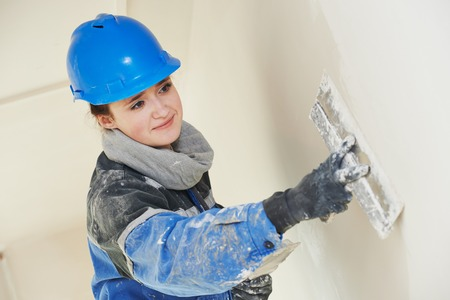 female plasterer painter at indoor wall renovation decoration stopping with spatula and plaster