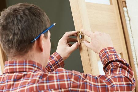 Male worker handyman carpenter at lock installation into wood door photo