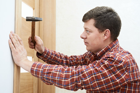Male handyman carpenter at interior wood door installation with hammer photo