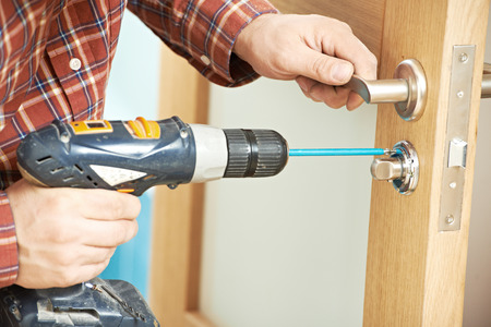 carpintero: carpintero en la instalaci�n de bloqueo con el taladro el�ctrico en la puerta de madera interior Foto de archivo