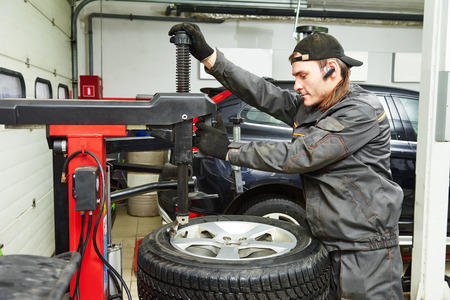 Auto repairman loading automobile car wheel at tyre fitting machine during tire replacing