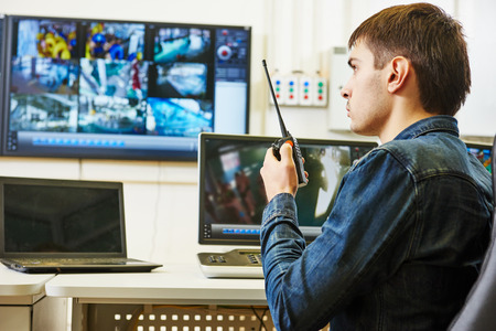 security room: security guard watching video monitoring surveillance security system Stock Photo