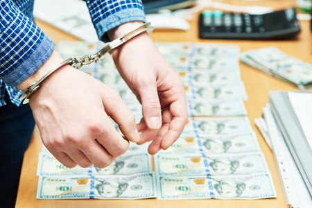 money bribe or corruption theme. male hands with dollars banknotes in handcuffs photo