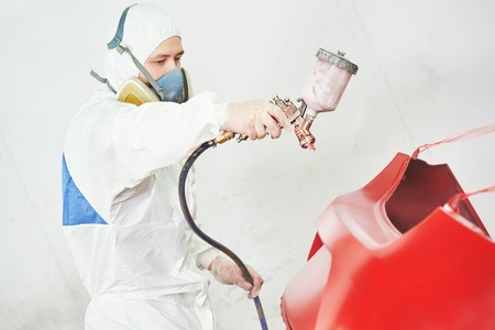 priming paint: auto mechanic worker painting a red car in a paint chamber during repair work