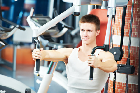 weight machine: fitness man at chest pectoral muscles exercises with training weight machine station in gym