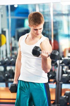 athlete man workout biceps brachii muscles exercises with training dumbbell in fitness gym photo