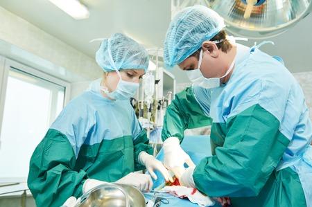 Cirujanos perfoming operación de cirugía de cesárea abdominal durante el parto parto en la clínica quirófano Foto de archivo - 37639998