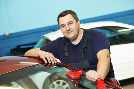 Automobile glazier repairman at  windscreen or windshield repair service shop