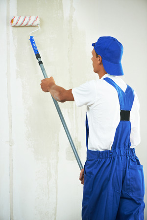 priming paint: One painter with paint roller making wall prime coating  at home repair renovation work Stock Photo