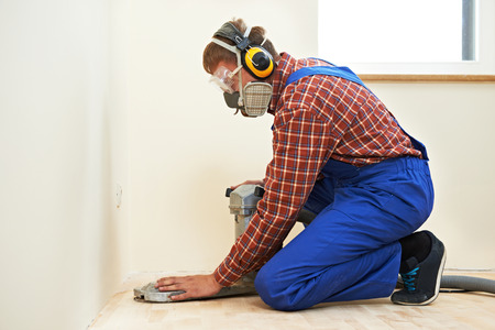 planking: carpenter doing parquet Wood Floor polishing maintenance work by grinding machine Stock Photo