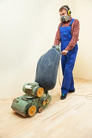craftman: carpenter doing parquet Wood Floor polishing maintenance work by grinding machine Stock Photo
