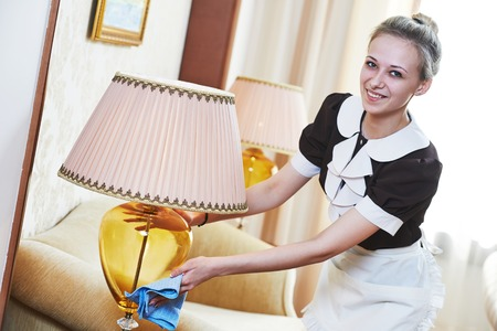 room service: Hotel service. female housekeeping worker with cleaning table from dust in room