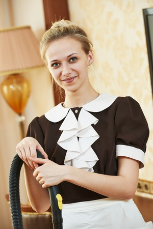 housemaid: Hotel service. Portrait of female housekeeping or housemaid with vacuum cleaner at inn room