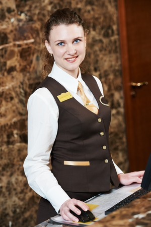 hotel worker: smiling female receptionist passing key card to guest