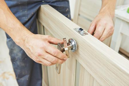 manejar: Carpintero manitas Macho en la instalación cerradura de la puerta interior de madera Foto de archivo