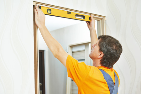 Male carpenter at interior wood door installation working with level