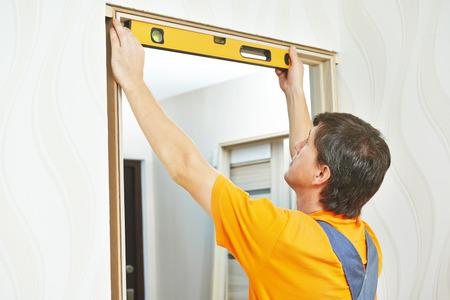 PUERTA: Carpintero de sexo masculino en la instalaci�n de la puerta interior de madera de trabajo con nivel